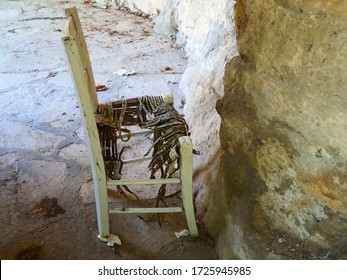 One old broken abadoned wooden rattan chair facing a stone wall in poor area of town