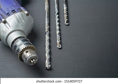 One old dirty scratched used electric drill or perforator near three messy augers for repair or other hard works lies on dark concrete table in workshop. Space for text