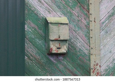 one old green metal mailbox hanging on a  wooden fence in the street
