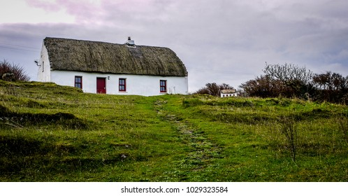 One old, thatched cottage in a field on a cloudy day. Taken in Inis More, Ireland.