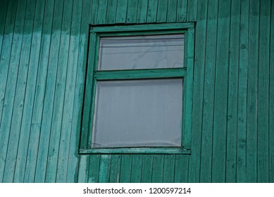 one old window on a green wooden wall
