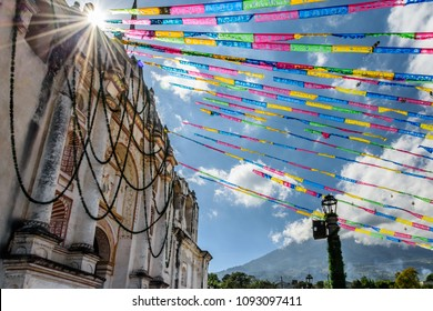 One of oldest Catholic churches in Guatemala in festive colors with Agua volcano behind. In small village outside Antigua, Guatemala's most famous Spanish colonial town & UNESCO World Heritage Site.