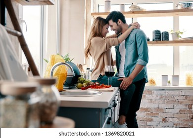 One and only. Beautiful young couple bonding face to face while standing in the kitchen at home