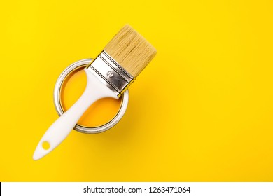 One open can of paint with white brush on it on yellow background. Top view. Repairing concept.