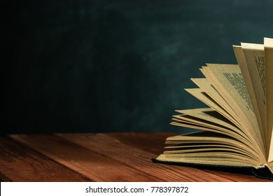 One open old book on a red wooden table. Beautiful dark background.