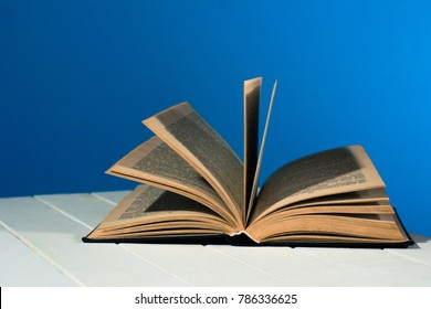One open old book on a red wooden table. Beautiful blue background.