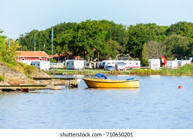 One open yellow motorboat moored to a pier with camping site in background. Location Karlskrona, Sweden.