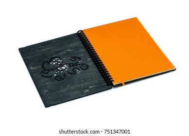 One opened black wooden notebook on a white background with a cut out pattern in the form of an octopus. Isolated on white.