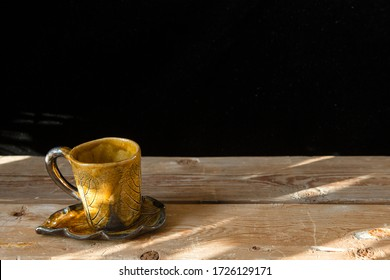 One orange hand made cup for coffee with saucer on the old wooden table and black background with sunshine and place for text