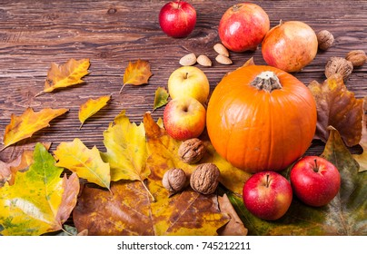 One orange pumpkin ,apples, walnuts and autumn leaves