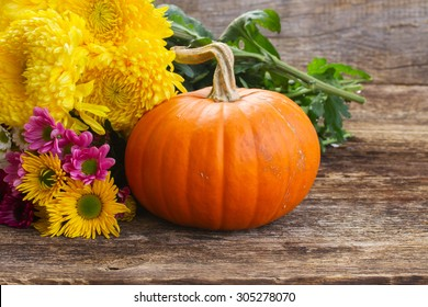 one orange pumpkin with mum flowers  on wooden textured  table