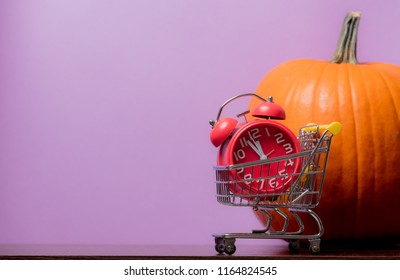 one orange pumpking and alarm clock with cart on purple background