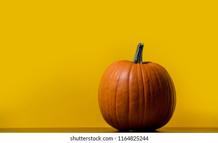 one orange pumpking on table with yellow background