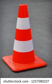 One orange and white traffic cone on the asphalt road