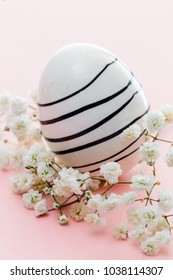 One painted easter egg on pink background with white flowers