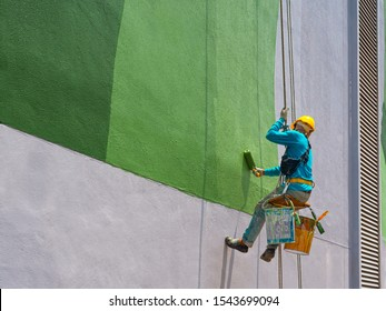 One painter is painting the exterior of the building on a dangerous looking scaffolding hanging from a tall building.