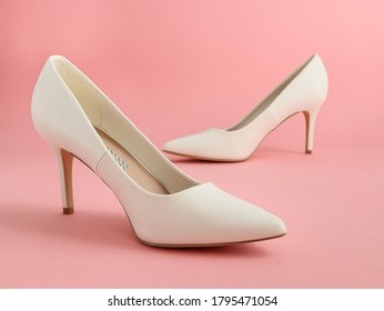 One pair of fashionable women's stiletto heels stand on a pink background, close-up side view.