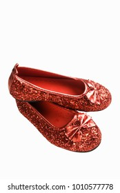 One pair of small red colored glittered slipper type shoes on a white background.
