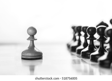 One pawn staying against full set of black chess pieces