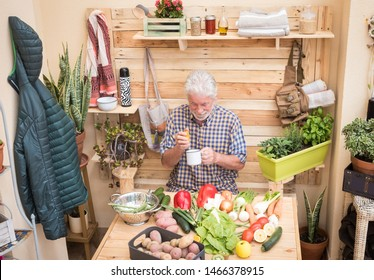 One people old man takes care of his health by drinking an orange juice. On the table a mix of vegetable of the garden waits to be cleaned