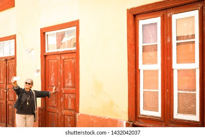 One people standing in front to a red vintage closed door. Rustic wooden windows and doors as per spanish tradition. One senior woman smiles and takes a selfie enjoying the trip