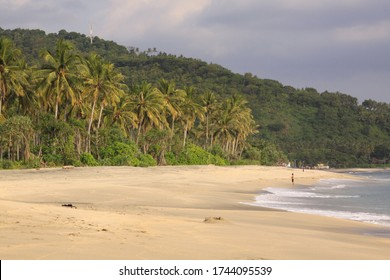 One person alone on empty beach at Pantai Setagi, near Senggigi, Lombok, Indonesia. Exotic tropical destination beach on island