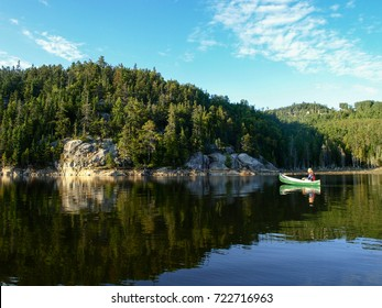 One person alone paddling in canoe on a beautiful lake in the parc of saguenay in Canada. Wild forest in the background.