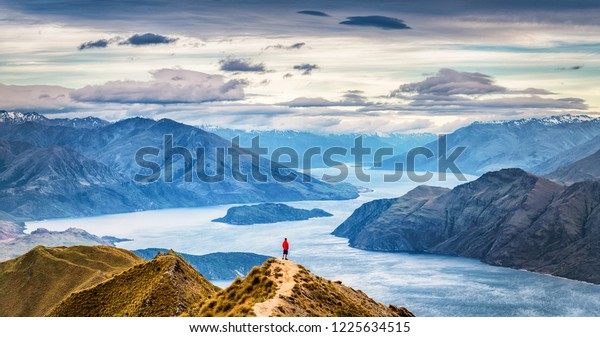 One person alone a the top of a mountain range with a lake and mountains in the background. New Zealand, Otago, South Island, Roys Peak, Wanaka; hiker