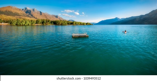 One person in a canoe at lake Wakatipu close to Glenorchy Wharf at sunset. Glenorchy is a charming alpine village in Otago region, New Zealand, South Island.