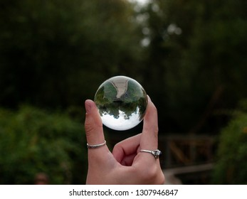 One person with a crystal ball in her hand in a forest in autumn