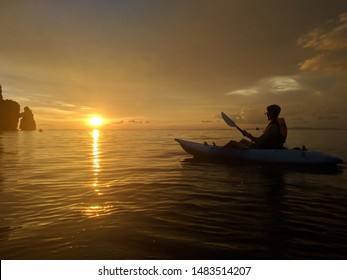 One person kayaking in the ocean with rocks and sunset in the background