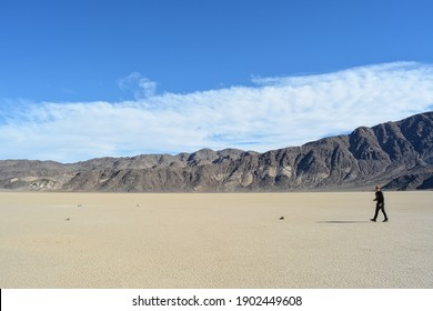 one person on the Racetrack Playa with moving stones leaving tracks in the dry and cracked terrain in the Death Valley National Park, recflections of the sun