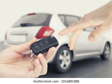 One person passing car keys to another person with car on background