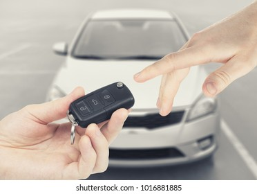 One person passing car-keys to another person with car on background