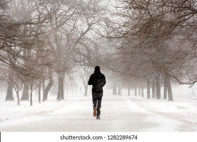 One person silhouette running/jogging in winter while a snow storm in the park along Lake Michigan, Chicago