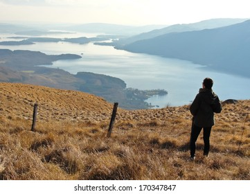One person standing on Ben Lomond looking at a panoramic view of Loch Lomond