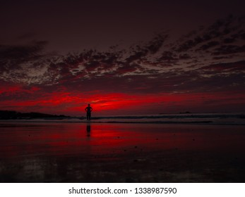 One person standing in waves and observing a beautiful sunset