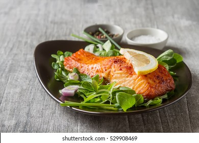 One piece of baked salmon grilled pepper lemon and salt on a brown plate with lettuce leaves. wood background