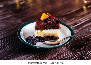One piece of cake with cream chocolate fruits sweet dessert with spoon on wooden background with bokeh lights