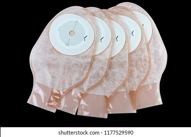 One piece drainable ileostomy or colostomy pouch products isolated on black background. Five pouch stoma care products on dark background. Transparent colostomy bag for colon or rectal cancer patients
