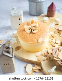 One piece of mini cheese cake with almond on top on wood tray for menu or bakery business. Selective focus.