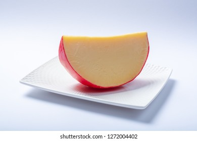One piece of traditional Dutch red ball Edam cheese close up on white background