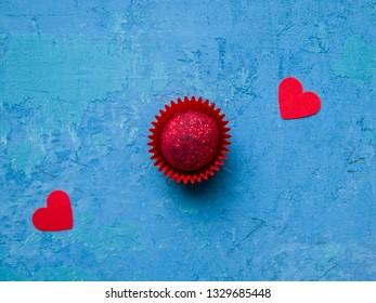 One pink chocolate truffle topped with sublimated raspberries on a bright blue concrete background. Next to this are two red hearts. Romantic concept.