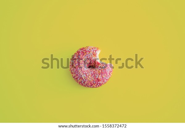 One pink donut bitten on yellow background