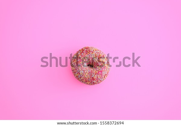 One pink donut on pink background