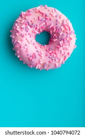 One pink donut on blue background.