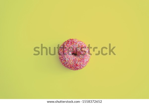 One pink donut on yellow background