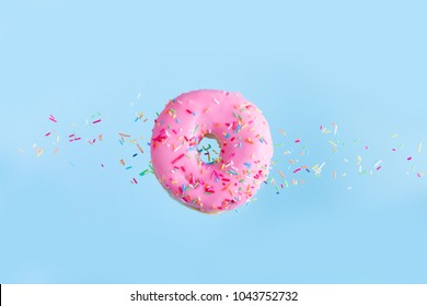 one pink flying sweet doughnut with sprincles on blue