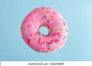 one pink flying sweet doughnut with blue background