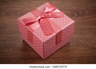 one pink gift box with a bow on a wooden background close up